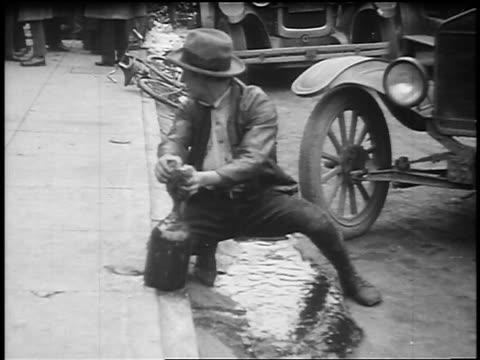 b/w 1920s man sponging liquor running in street until cop stops him / prohibition / feature film - 禁酒法点の映像素材/bロール