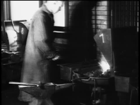 stockvideo's en b-roll-footage met b/w 1920s man stoking fire + using hammer + anvil in vocational school / newsreel - alleen één tienerjongen