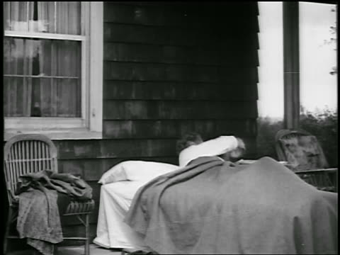 B/W 1920s man waking up in bed on front porch of house / educational