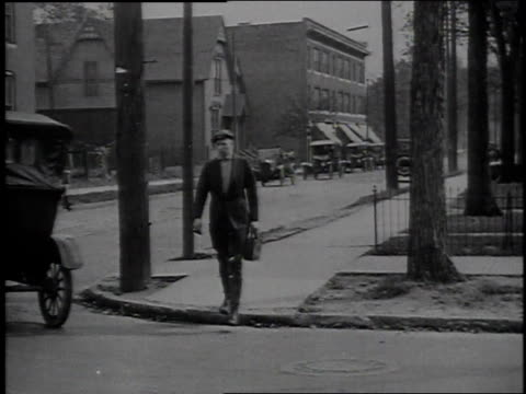 1920s ws man walking across the street is hit by car / united states - pedestrian stock videos & royalty-free footage