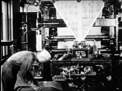 b/w 1920s man working by printing presses in newspaper printing plant / newsreel - 1920 stock videos & royalty-free footage