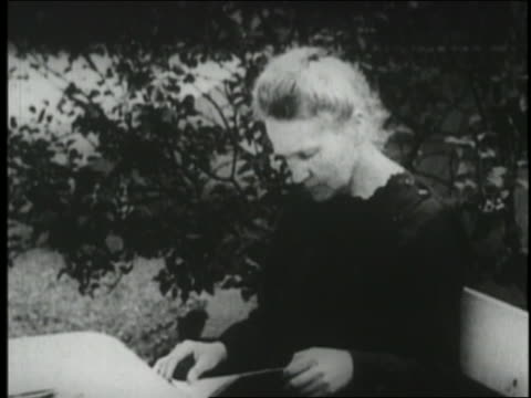 1920s marie curie in black dress sitting outside looking at book - black dress stock videos & royalty-free footage