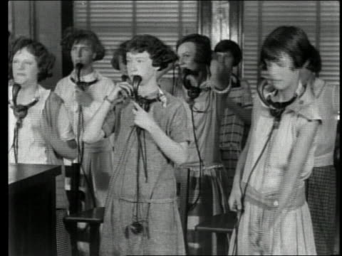 stockvideo's en b-roll-footage met 1920s medium shot young women telephone operator trainees removing head sets and wrapping up cords - 20 29 jaar