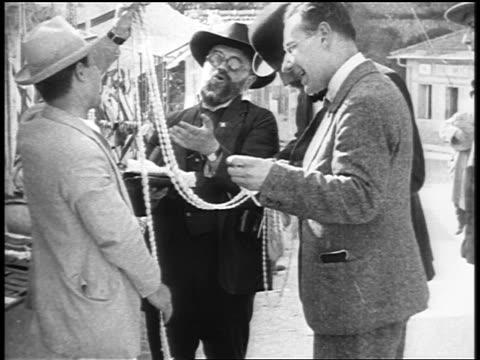 stockvideo's en b-roll-footage met b/w 1920s men bargaining over beads at outdoor marketplace / paris / documentary - men