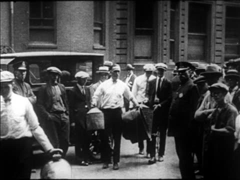 b/w 1920s men carrying captured still equipment on city street / boston / prohibition / newsreel - 1920 stock videos & royalty-free footage