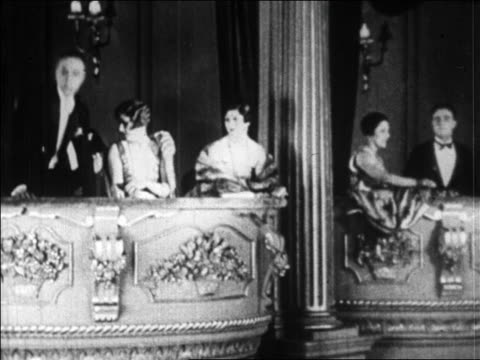 vidéos et rushes de b/w 1920s men in tuxedos standing up in box seats of theater as women look on / paris / newsreel - stéréotype de la classe supérieure