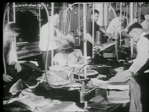 B/W 1920s men ironing clothing in clothing factory