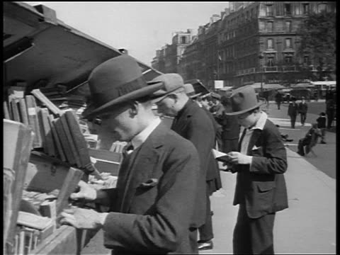 B/W 1920s men looking at books at outdoor book stall / Paris / documentary