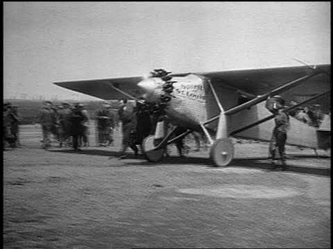 b/w 1920s men running holding onto spirit of st louis airplane while taxiing - charles lindbergh stock videos & royalty-free footage