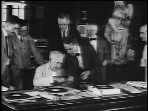 B/W 1920s men talking to senior Thomas Edison as he inspects records in factory