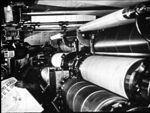 B/W 1920s men working by rolling printing press in newspaper printing plant / newsreel