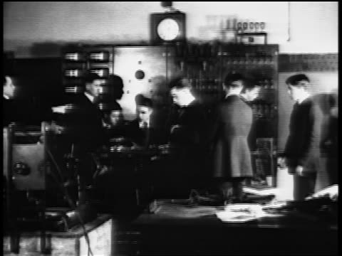 b/w 1920s men working in control room of electronics class in vocational school / newsreel - audio electronics stock videos & royalty-free footage
