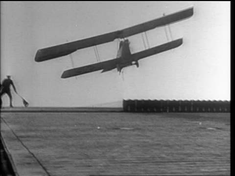 b/w 1920s pan military prop bi-plane crashes on landing on early aircraft carrier - airplane crash stock videos and b-roll footage