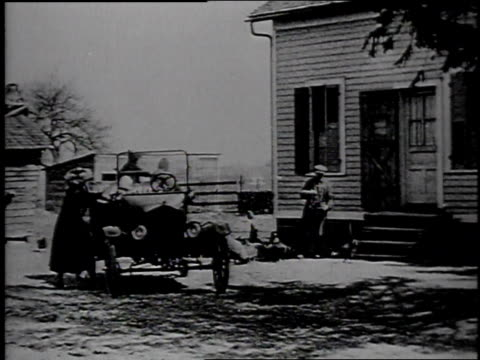 1920s montage farmers wife holding baby getting in car and driving off farm to visit neighbor / united states - フォード・t型モデル点の映像素材/bロール