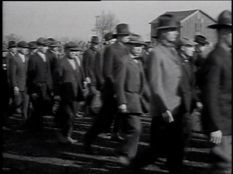 1920s MONTAGE military recruits playing tug of war with a large medicine ball / United States
