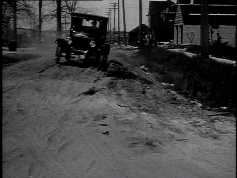 1920s montage model t car driving on rough road, through small stream, and through snow / united states - フォード・t型モデル点の映像素材/bロール