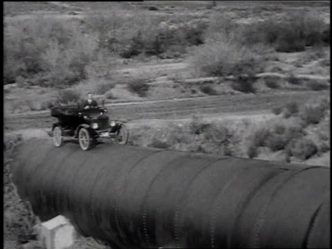 1920s montage model t car driving very slowly up a steep hill on top of massive pipe / united states - model t stock videos and b-roll footage