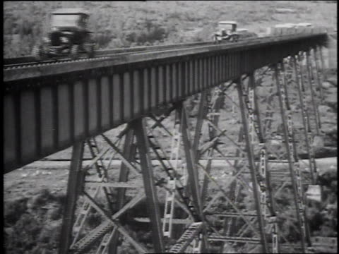 1920s montage model t cars driving across bridge on railroad tracks / united states - model t stock videos and b-roll footage
