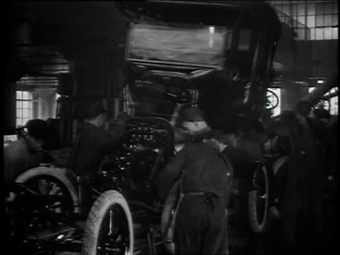 1920s MONTAGE Workers on an assembly line building Model T cars then man driving it off lift / Detroit, Michigan, United States