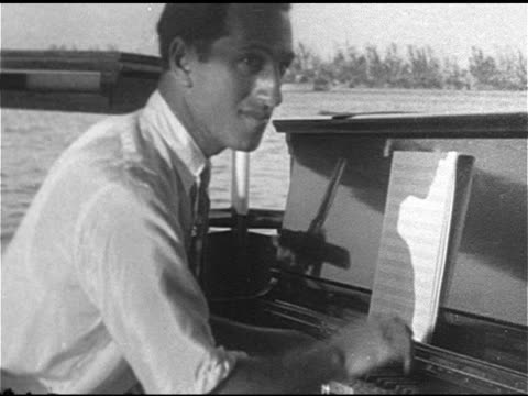 MUSIC Composer pianist George Gershwin playing upright piano on boat w/ two unidentified men MS George playing HA WS George playing on grand piano w/...