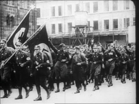 B/W 1920s Nazis in uniform marching on street raising arms in salute / documentary