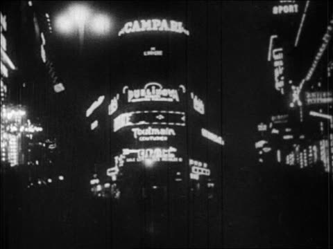 b/w 1920s neon lights on city street corner at night / paris, france / newsreel - 1920 stock videos & royalty-free footage