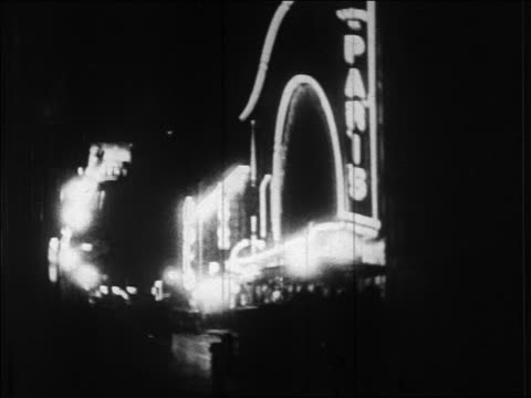 B/W 1920s neon lights on theater marquee at night / Paris, France / newsreel