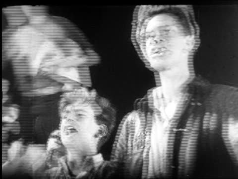 b/w 1920s newspaper boys running / dissolve to faces of newsboys shouting / newsreel - shouting stock videos & royalty-free footage