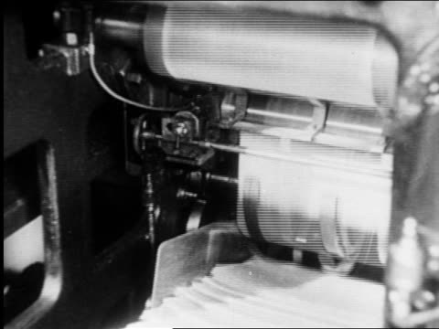 b/w 1920s newspapers moving off printing press in factory / dissolve to newsboys shouting / newsreel - druckmaschine stock-videos und b-roll-filmmaterial