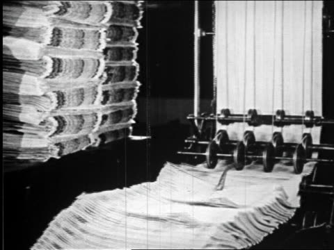 b/w 1920s newspapers rolling off of presses in newspaper printing plant / newsreel - nachrichtenredaktion stock-videos und b-roll-filmmaterial