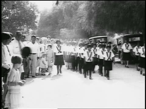 B/W 1920s parade of Native American schoolchildren in uniform / educational