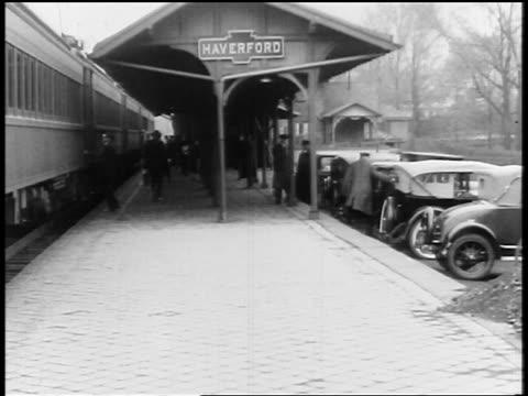 vídeos de stock, filmes e b-roll de b/w 1920s people getting off train at train station / haverford, pennsylvania / newsreel - capa de chuva
