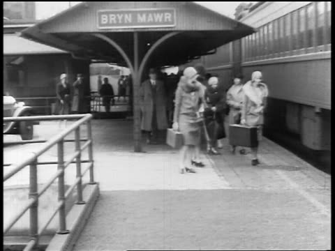 stockvideo's en b-roll-footage met b/w 1920s people getting on train at station / bryn mawr, pa / newsreel - passenger train