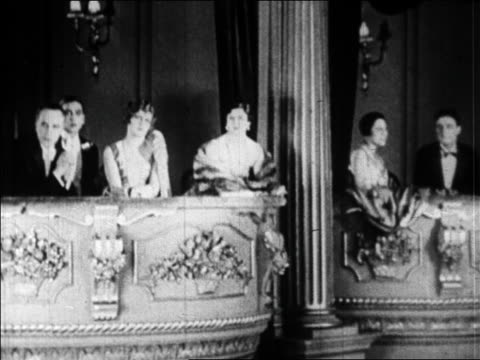 vidéos et rushes de b/w 1920s people in formalwear sitting in box seats in theater / paris / newsreel - stéréotype de la classe supérieure