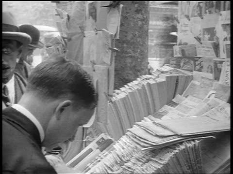 B/W 1920s people looking at books + pamphlets at outdoor market stall / Paris, France / documentary