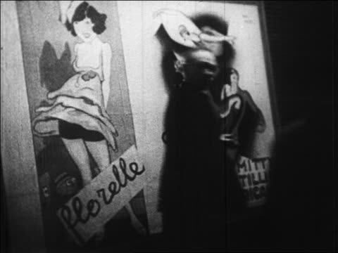 "b/w 1920s people passing ""casino de paris"" poster on street at night / paris, france / newsreel - casino poster stock videos & royalty-free footage"