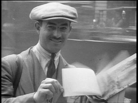 b/w 1920s portrait man with mustache + hat showing postcard book to camera outdoors / paris / doc. - salesman stock videos & royalty-free footage