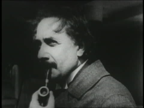 1920s profile close up young albert einstein smoking pipe + smiling - アルバート・アインシュタイン点の映像素材/bロール