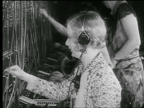 B/W 1920s PROFILE line of telephone switchboard operators / newsreel
