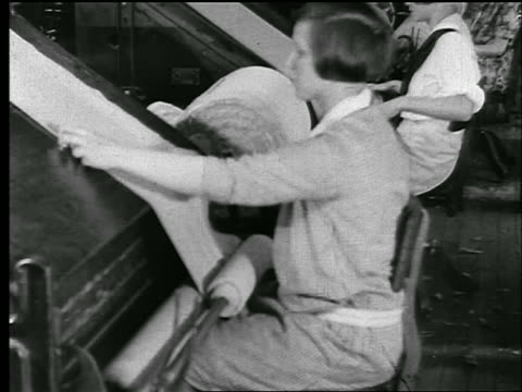 b/w 1920s profile woman works with bolt of cloth at table in textile/clothing factory / newsreel - 織物工場点の映像素材/bロール