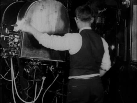 B/W 1920s projectionist operating projector in booth
