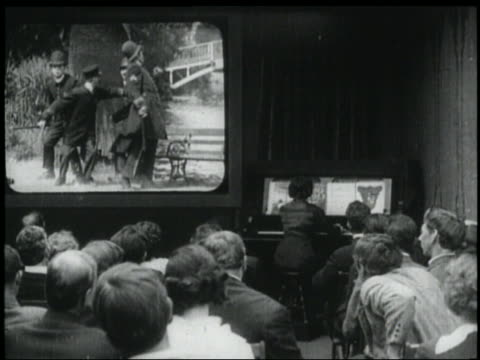 b/w 1920s rear view audience watches keystone cops movie in theater / 1 man claps + gestures - 1920 stock videos & royalty-free footage