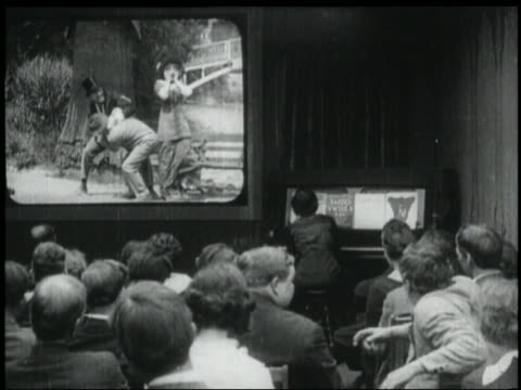 B/W 1920s REAR VIEW audience watches movie in theater / 1 man stands up + gestures excitedly