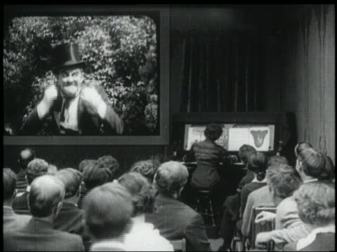 b/w 1920s rear view audience watching villain movie in theater - schurke stock-videos und b-roll-filmmaterial