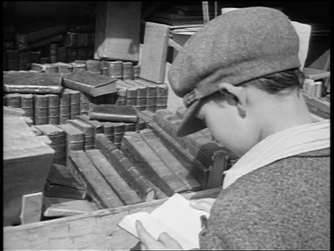 B/W 1920s REAR VIEW close up boy with hat looking at books at outdoor book stall / Paris / documentary