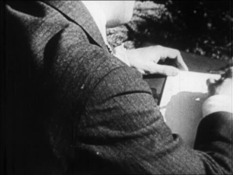 b/w 1920s rear view close up overtheshoulder f scott fitzgerald writing at desk outdoors / france / newsreel - f. scott fitzgerald writer stock videos and b-roll footage