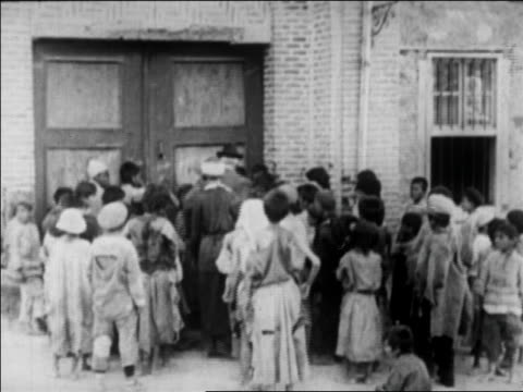 b/w 1920s rear view crowd of children standing at door of orphanage as 2 adults open door - orphan stock videos & royalty-free footage