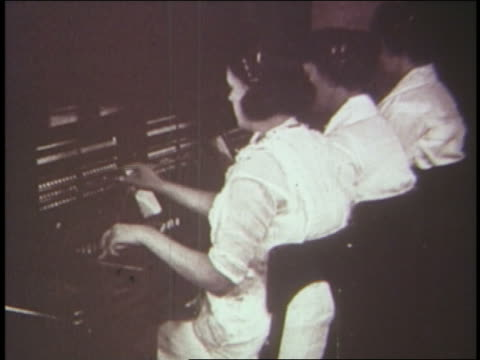 b/w 1920s rear view female telephone operators - getönt stock-videos und b-roll-filmmaterial