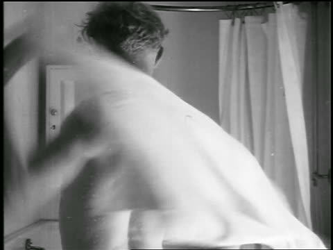 b/w 1920s rear view man drying off with towel in bathroom after shower / educational - drying stock videos and b-roll footage
