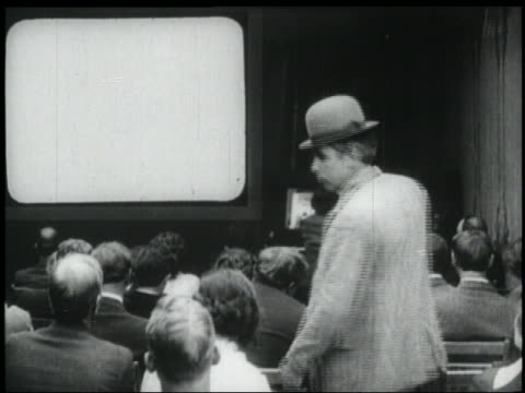 b/w 1920s rear view man (mack sennett) enters movie theater with piano player + sits down - projection equipment stock videos & royalty-free footage